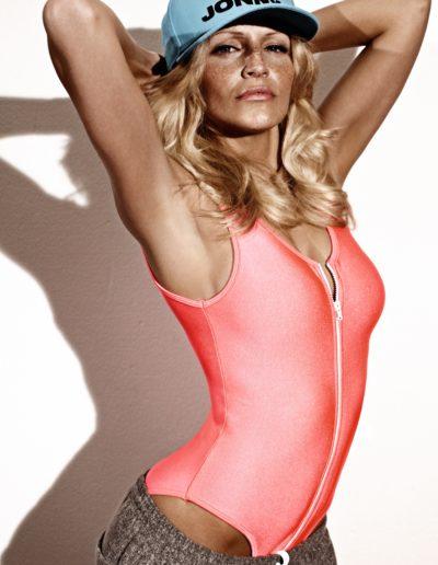 attraktive Frau posiert vor weißer Wand in Sportoutfit