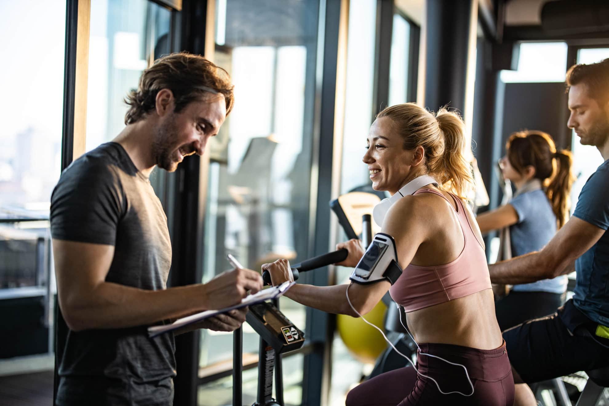 Glückliche Frau, die auf einem stationären Fahrrad in einem Fitnessstudio trainiert und auf ihren Trainer schaut, der Pläne für ihre zukünftigen Sporttrainings macht